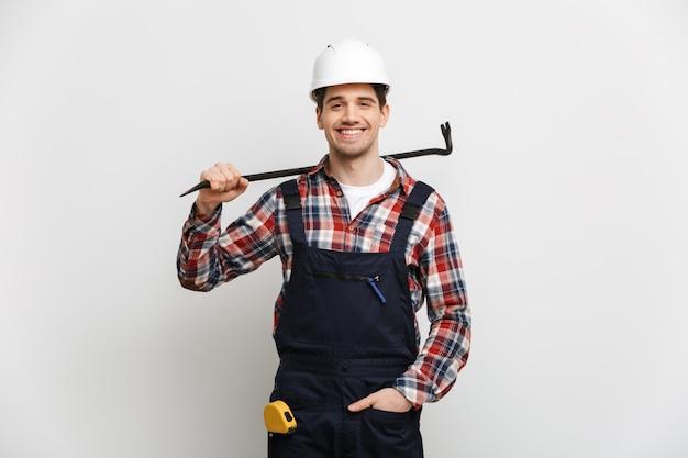 Glimlachende mannelijke bouwer in de beschermende koevoet van de helmholding over grijze muur