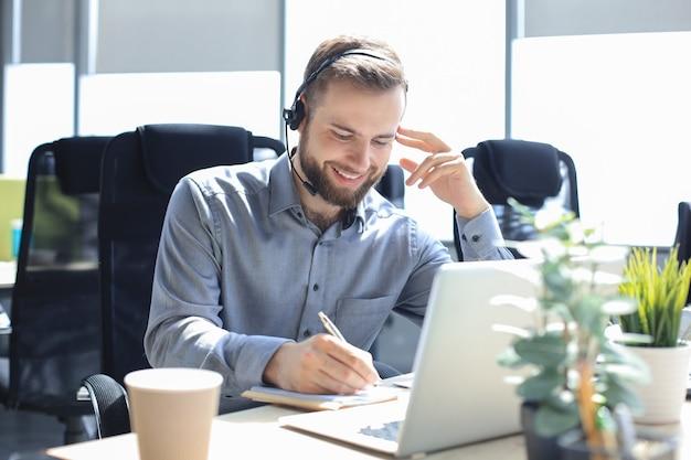 Glimlachende mannelijke callcenter-operator met koptelefoon zittend op een modern kantoor, online informatie raadplegend op een laptop, informatie opzoeken in een bestand om de klant te helpen.