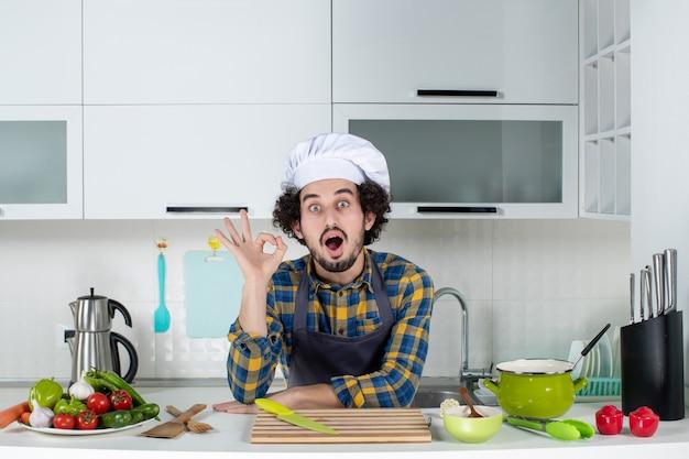 Glimlachende mannelijke chef-kok met verse groenten die een brilgebaar maken in de witte keuken