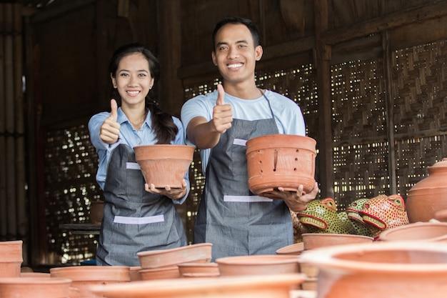 Glimlachende mannelijke en vrouwelijke pottenbakker die hun product in aardewerk houden