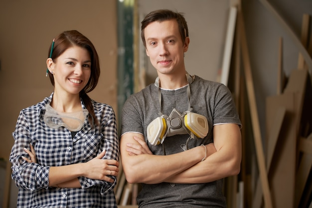 Glimlachende mannelijke en vrouwelijke schrijnwerkers met gekruiste armen in werkplaats