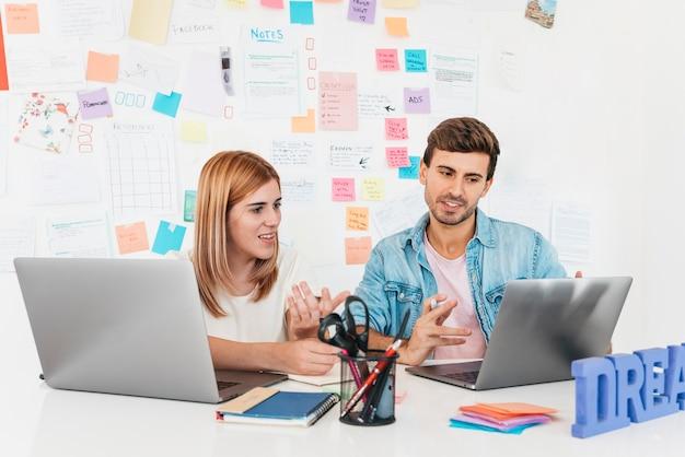 Glimlachende mannelijke en vrouwelijke zitting bij bureau en het spreken die laptop bekijken
