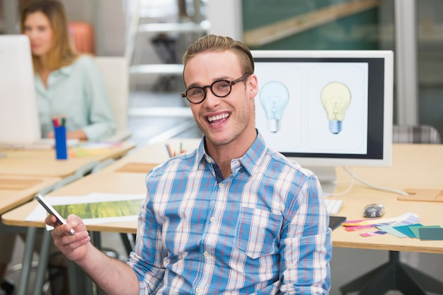 Glimlachende mannelijke fotoredacteur in bureau