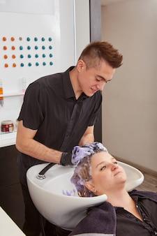 Glimlachende mannelijke kapper die vrouwenhaar in salon verstevigt
