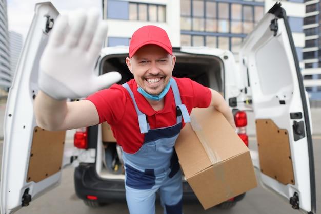 Glimlachende mannelijke koerier met grote kartonnen doos op de achtergrond van de auto holding