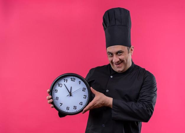 Glimlachende mannelijke kok op middelbare leeftijd in de muurklok van de chef-kok eenvormige holding met exemplaarruimte