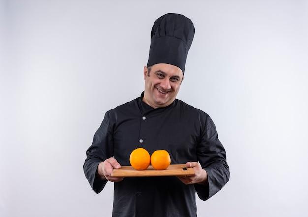 Glimlachende mannelijke kok op middelbare leeftijd in de sinaasappelen van de chef-kok de eenvormige holding op scherpe raad