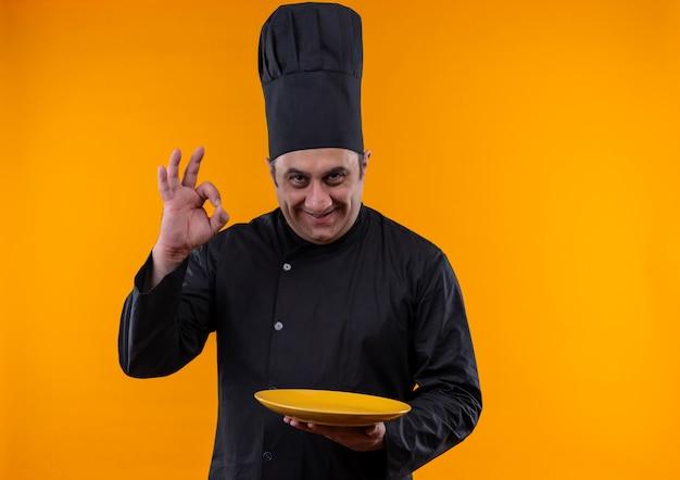 Glimlachende mannelijke kok op middelbare leeftijd in eenvormige chef-kok die de plaat van de okeygebaarholding op gele achtergrond met exemplaarruimte toont