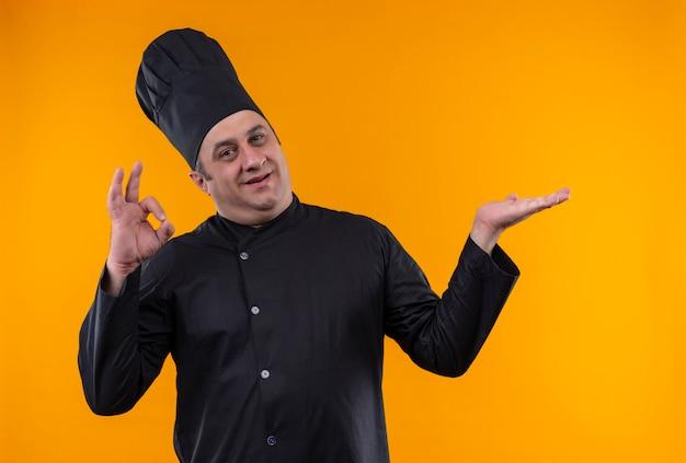 Glimlachende mannelijke kok op middelbare leeftijd in eenvormige chef-kok die okey op gele achtergrond met exemplaarruimte toont