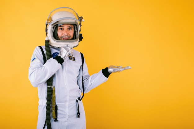 Glimlachende mannelijke kosmonaut in ruimtepak en helm, wijzend met hand naar rechts, op gele muur.