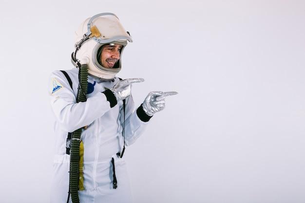 Glimlachende mannelijke kosmonaut in ruimtepak en helm, wijzend met hand naar rechts, op witte achtergrond.