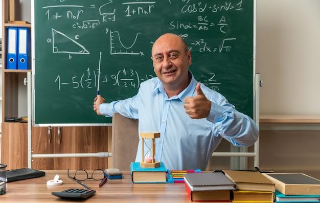 Glimlachende mannelijke leraar van middelbare leeftijd zit aan tafel met schoolhulpmiddelen op het bord met een aanwijzer die de duim in de klas laat zien Gratis Foto