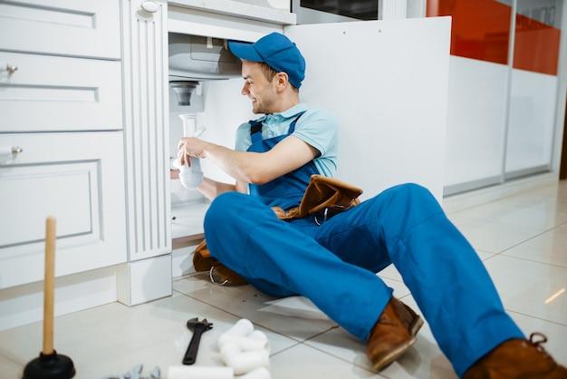 Glimlachende mannelijke loodgieter in uniform houdt afvoerpijp in de keuken. klusjesvrouw met gereedschapstas reparatie gootsteen, sanitair service aan huis