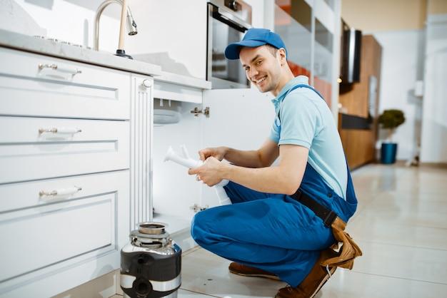 Glimlachende mannelijke loodgieter in uniform houdt afvoerpijp in de keuken. klusjesvrouw met gereedschapstas reparatie gootsteen, sanitair service thuis