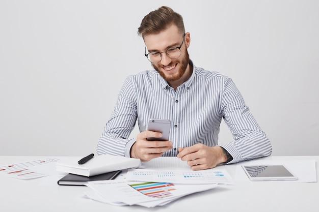 Glimlachende mannelijke manager omringd met veel papieren en gadgets, ontvangt gefeliciteerd met de mobiele telefoon van vriend zoals verjaardag