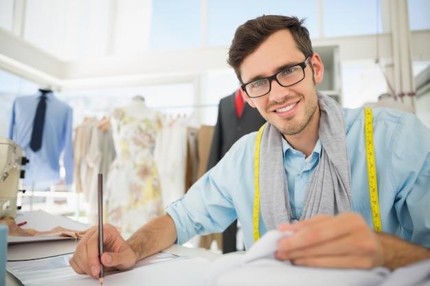 Glimlachende mannelijke manierontwerper die aan zijn ontwerpen werken
