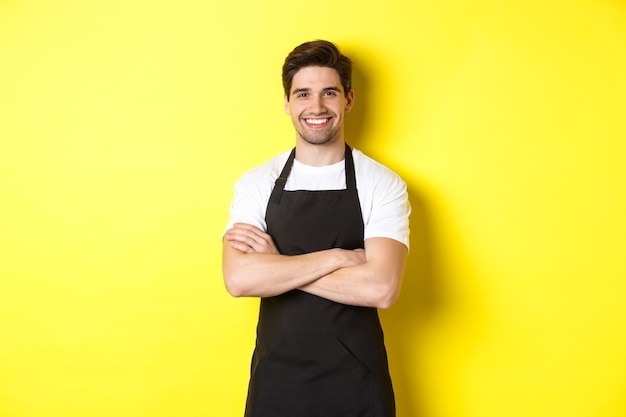 Glimlachende mannelijke ober in zwarte schort staande zelfverzekerde kruisarmen op de borst tegen een gele achtergrond