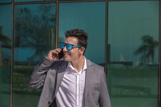 Glimlachende mannelijke ondernemer die op mobiele telefoon op straat spreekt