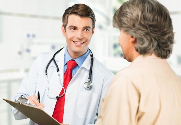 Glimlachende mannelijke patiënt met arts op achtergrond