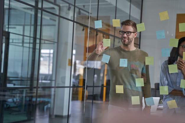 Glimlachende mannelijke persoon die in een zakelijk bedrijf werkt