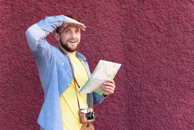 Glimlachende mannelijke reizigersfotograaf die zijn ogen met holdingskaart beschermen die zich tegen geweven muur bevinden