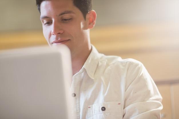 Glimlachende mannelijke student die laptop in lezingszaal met behulp van