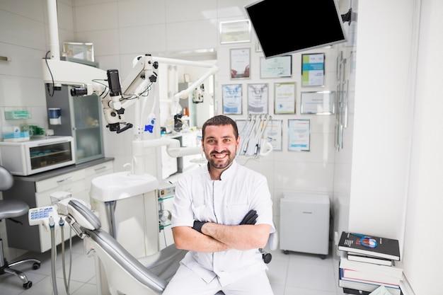 Glimlachende mannelijke tandarts die in kliniek camera bekijken