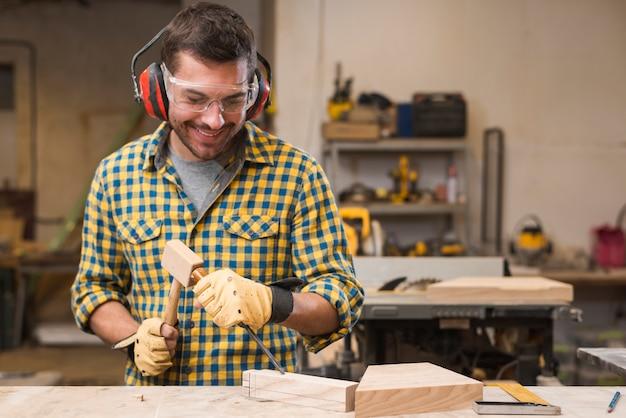 Glimlachende mannelijke timmerman die de beitel in het houten blok raken