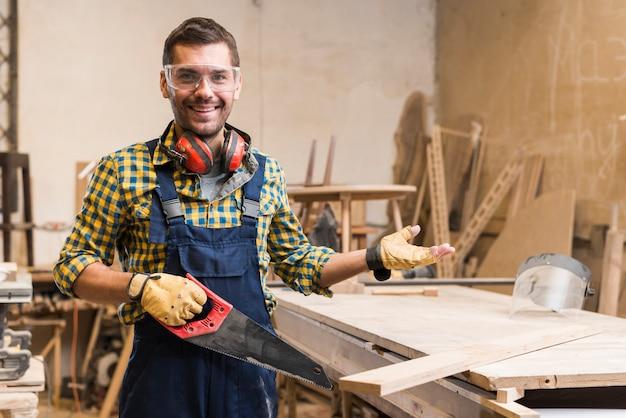 Glimlachende mannelijke timmerman die veiligheidsbril draagt die handsaw het gesturing houdt
