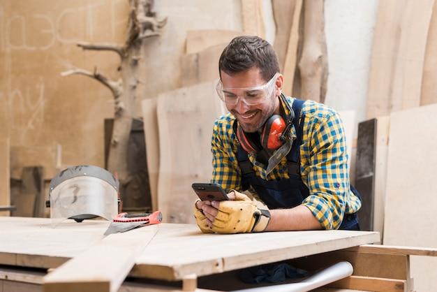 Glimlachende mannelijke timmerman die veiligheidsglazen en oorverdediger dragen rond zijn hals die cellphone gebruiken