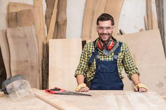 Glimlachende mannelijke timmerman die zich achter de werkbank bevindt