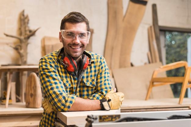 Glimlachende mannelijke timmerman met oorverdediger rond haar hals die zich in zijn workshop bevinden