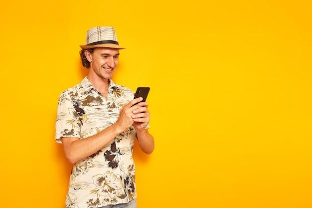 Glimlachende mannelijke toerist op vakantie met telefoon in zijn handen schrijft bericht geïsoleerde gele achtergrond