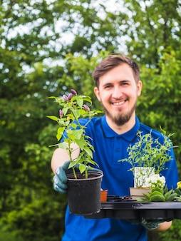 Glimlachende mannelijke tuinman die potteninstallatie in zijn hand toont