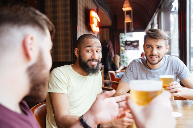 Glimlachende mannelijke vrienden praten en bier drinken in de pub