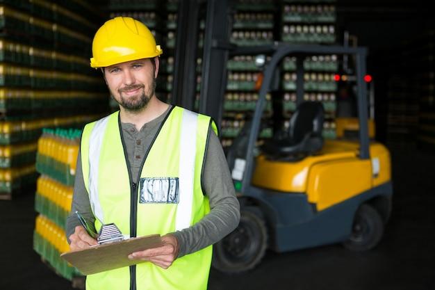 Glimlachende mannelijke werknemer die op klembord in magazijn schrijft