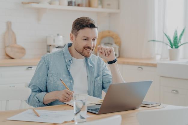 Glimlachende mannelijke werknemer die thuis laptop gebruikt, aan de keukentafel zit, naar het scherm kijkt en videogesprekken voert of webinars bekijkt, notities schrijft in notitieblok. afstandsstudie en freelance concept