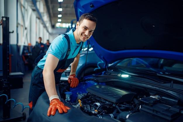 Glimlachende mannelijke werknemer in uniform controleert voertuigmotor, autoservicestation. automobielcontrole en inspectie, professionele diagnostiek en reparatie