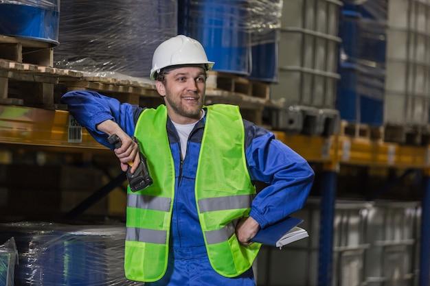 Glimlachende mannelijke werknemer met barcodelezer leunend op plank met hand met notebook op taille staande in magazijn.