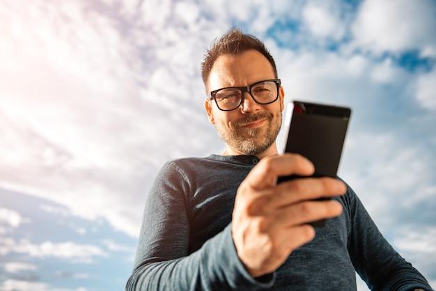 Glimlachende mannen die tekstbericht typen