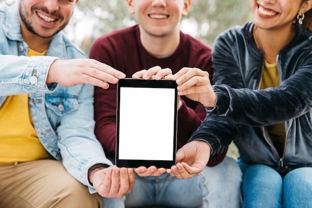 Glimlachende mannen en vrouw die tablet samen tonen