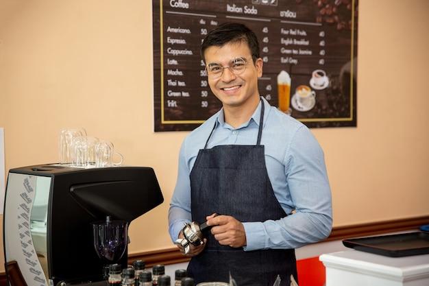 Glimlachende mannen permanent koffiezetapparaat in coffeeshop als eigenaar van een klein bedrijf.