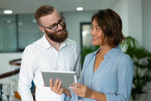 Glimlachende marketingspecialisten die statistische gegevens analyseren