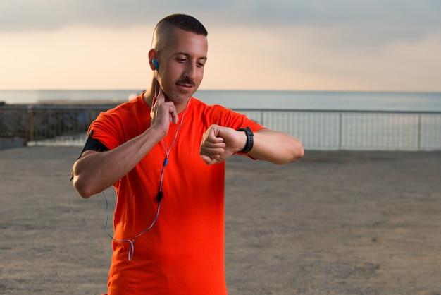Glimlachende medio volwassen mannelijke atleet kijken naar horloge