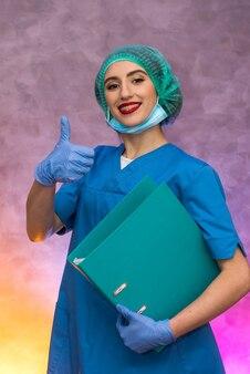 Glimlachende medische arbeider die grote omslag houdt. vrouw in medisch uniform poseren in het ziekenhuis