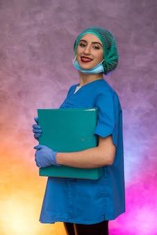 Glimlachende medische werker die grote map houdt. vrouw in medisch uniform poseren in het ziekenhuis