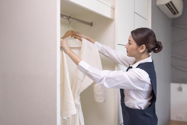Glimlachende meid met witte badjas met hanger in kleerkast, het concept van het hotelwezen