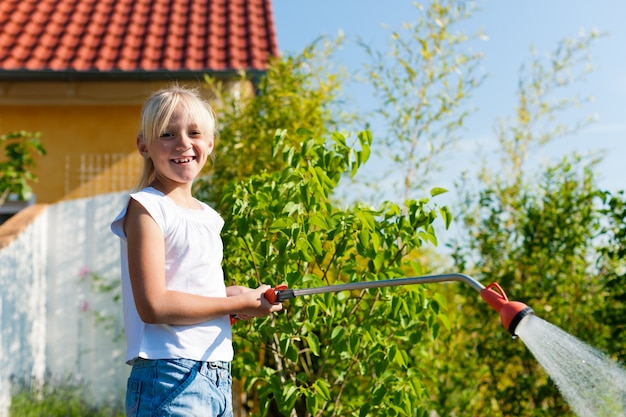 Glimlachende meisje het water geven installaties in de tuin