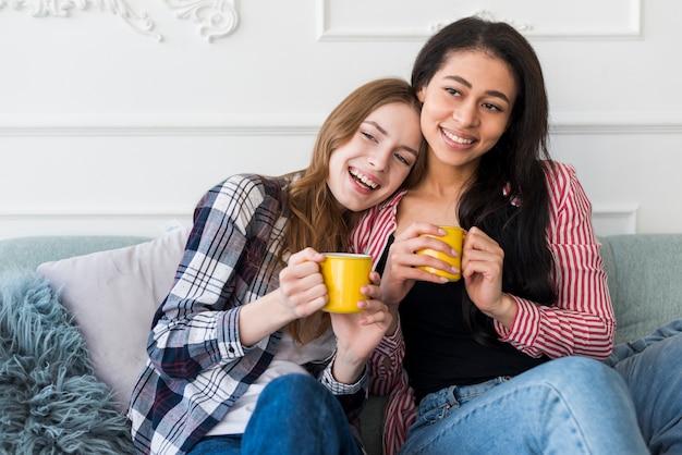 Glimlachende meisjes die dichtbij zitten en gele koppen in handen houden