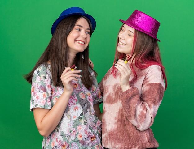 Glimlachende meisjes die een feestmuts dragen en een feestfluitje vasthouden, kijken elkaar aan, geïsoleerd op een groene muur